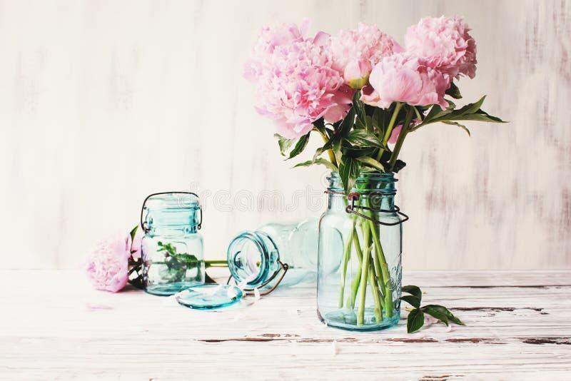 在一个古色古香的金属螺盖玻璃瓶的Farnhouse桃红色牡丹 库存照片