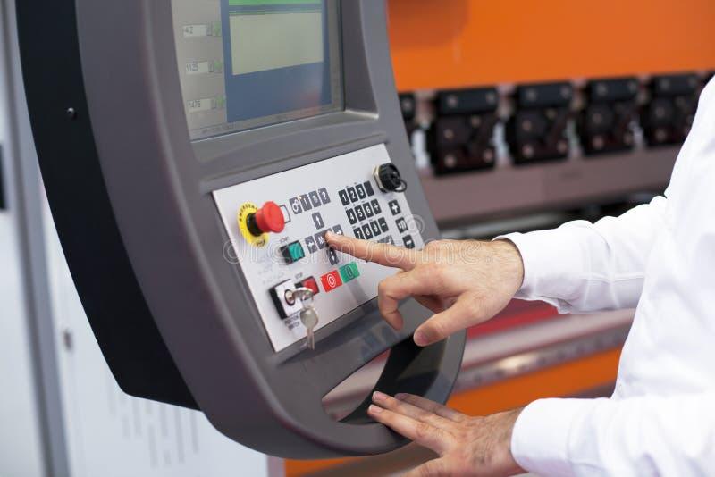在一个可编程序的机器的控制板的手 库存照片