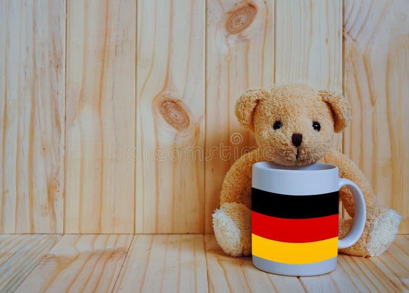 在一个咖啡杯的德国旗子有玩具熊和木背景的 库存照片