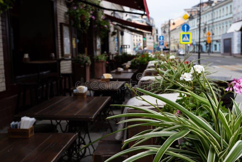 在一个咖啡馆之外的街道桌在背景中是defocused在前景,花叶子  免版税库存图片