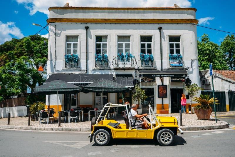 在一个咖啡馆前面停放的黄色儿童车在畔井,葡萄牙迷人的村庄  库存图片