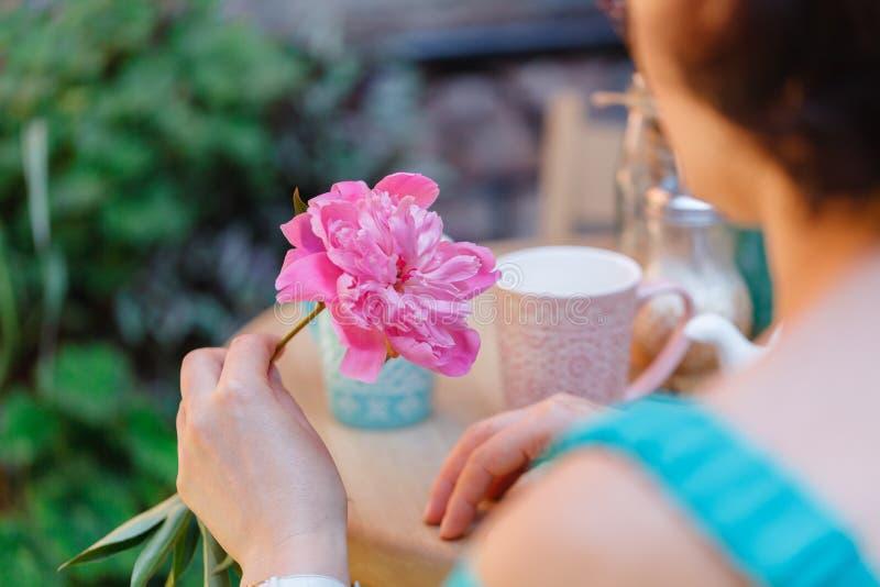 在一个咖啡馆的妇女坐的饮用的茶与花在手中 免版税库存照片