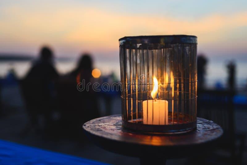在一个咖啡馆的浪漫晚餐在日落的海洋 一个蜡烛在客人的一张桌上烧咖啡馆的 图库摄影