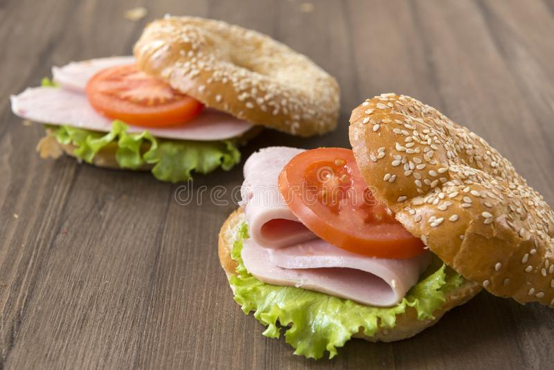 在一个圆的小圆面包的三明治与芝麻、2个三明治用火腿,蕃茄和莴苣 库存图片