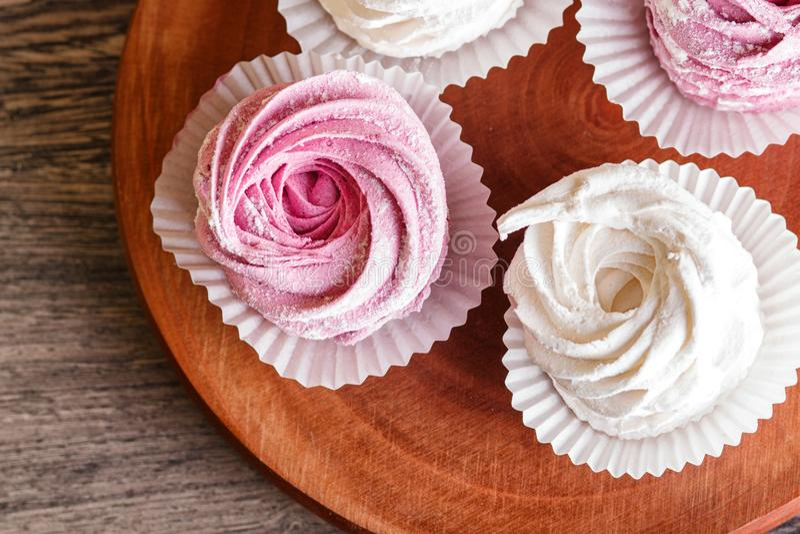 在一个圆的木板的桃红色和白色蛋白软糖 免版税库存图片