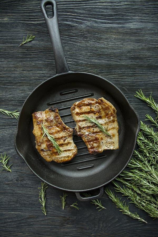 在一个圆的格栅平底锅的烤牛排,装饰用肉、迷迭香、绿色和菜的香料在黑暗的木背景 免版税图库摄影