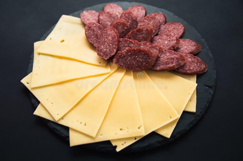 在一个圆的石黑人委员会的被切的乳酪和蒜味咸腊肠香肠谎言 在黑背景的乳酪切片 香肠在回合切了 库存照片