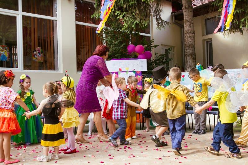 在一个圈子的幼儿园老师跳舞与老师 免版税库存照片