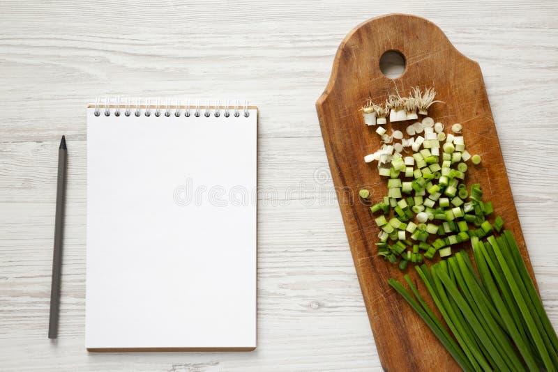 在一个土气木板的被切的大葱,与铅笔的空白的笔记薄在白色木表面,顶视图 顶上,平的位置, 图库摄影