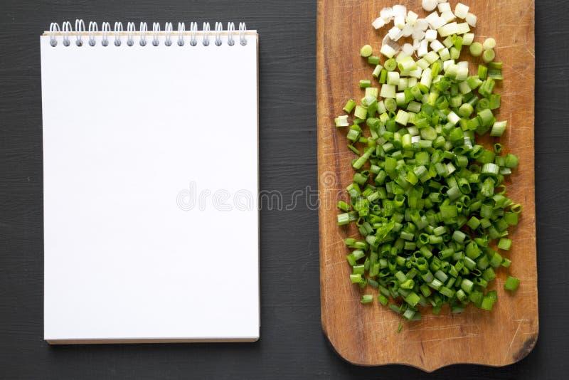 在一个土气木板的被切的大葱,在黑背景的空白的笔记薄,顶视图 r 库存图片