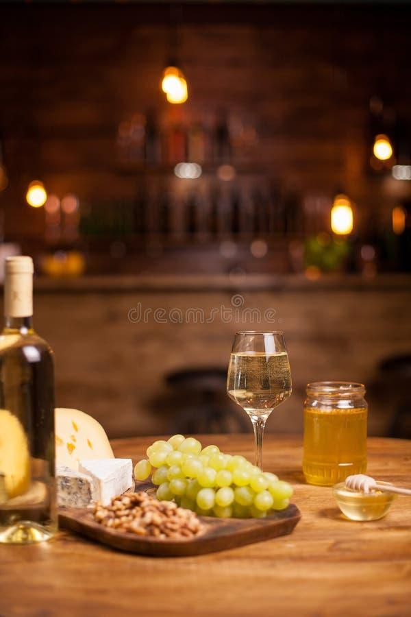 在一个土气木盛肉盘的可口白葡萄在鲜美核桃旁边 库存图片