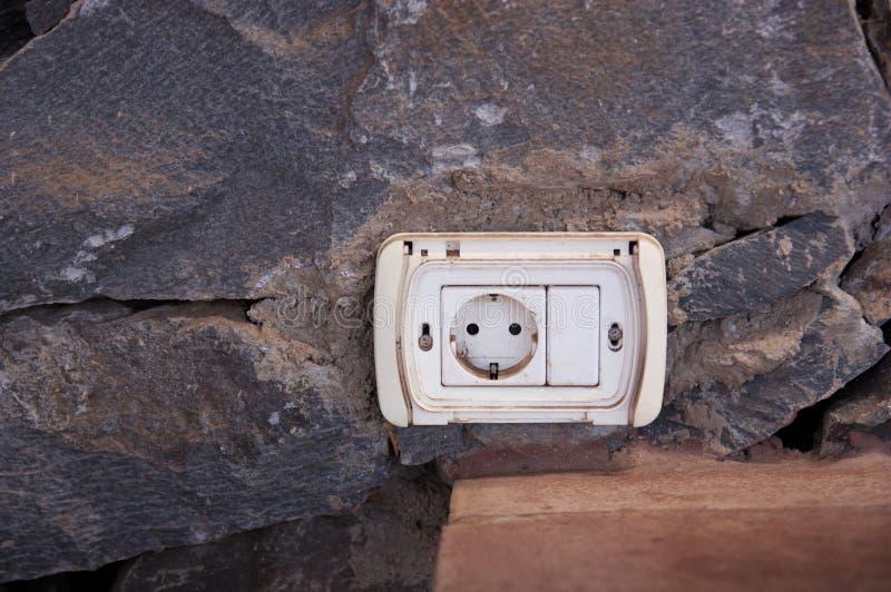 在一个土气石墙安置的一个年迈的插座 图库摄影