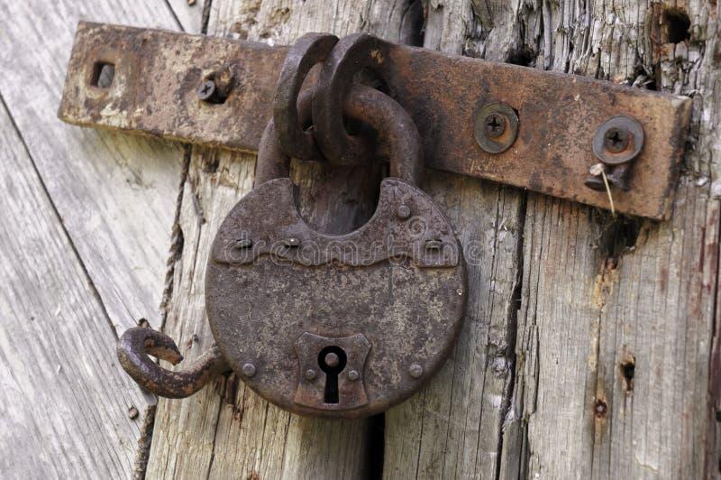 在一个土气门的老生锈的锁与装饰自然被风化的木板条 免版税库存照片