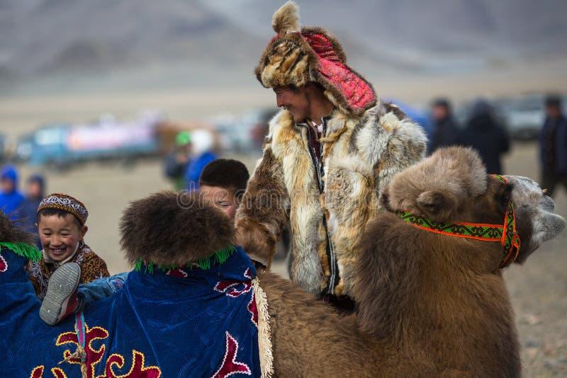 在一个地方假日期间,地方哈萨克人人在骆驼乘坐孩子 免版税图库摄影
