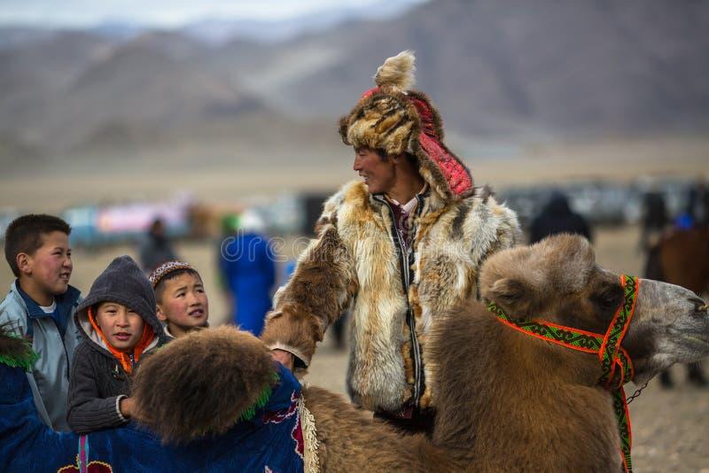 在一个地方假日期间,地方哈萨克人人在骆驼乘坐孩子 图库摄影