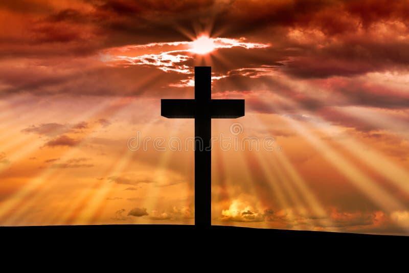在一个场面的耶稣基督木十字架与深红橙色日落, 免版税库存照片