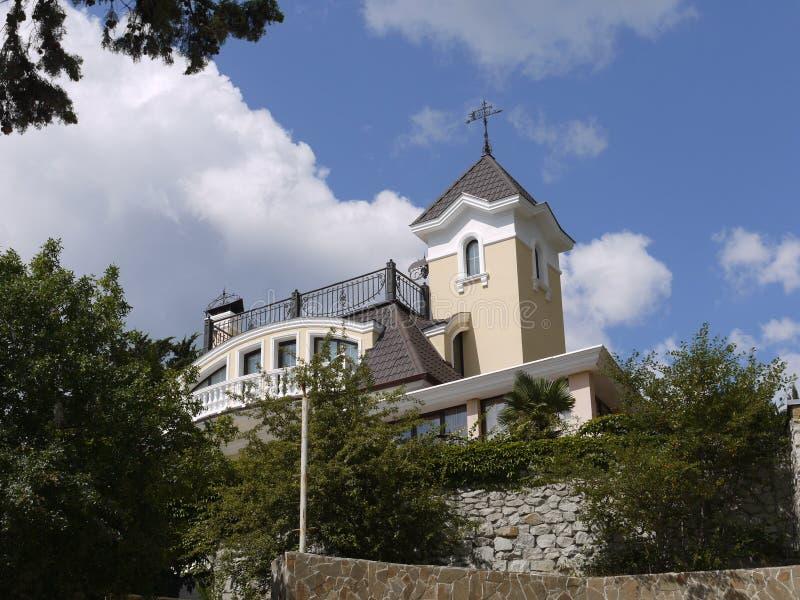 在一个城堡样式的一个富有的豪宅与在一个高石墙后的一栋塔楼,围拢由绿色树和灌木反对 免版税库存图片