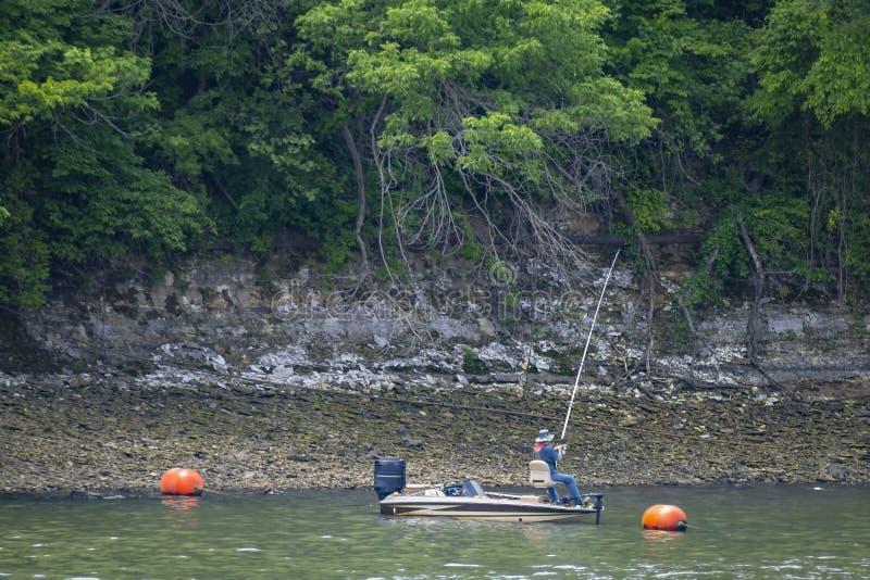 在一个外置马达渔船的一人渔在一个高堤防下的bouys附近与许多非常绿色树上升高 库存图片