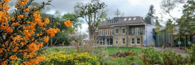 在一个多云春日采取的全景Pinner纪念公园、英国、西部议院和荒地鲁宾逊博物馆在背景中 免版税库存照片