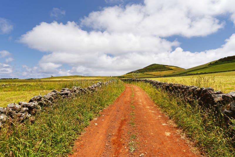 在一个多小山风景的红色车道 免版税库存照片