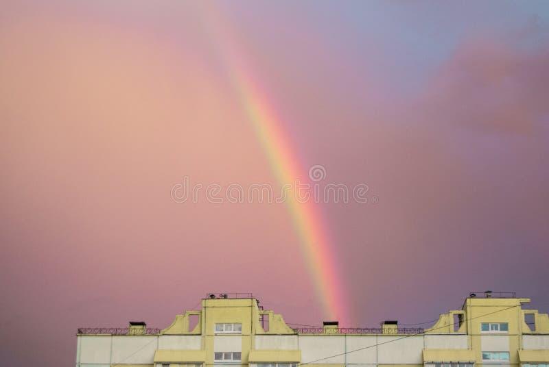 在一个多层的城市房子的屋顶的彩虹平衡的桃红色日落天空的在雨以后,意想不到地美好的夏天 库存照片