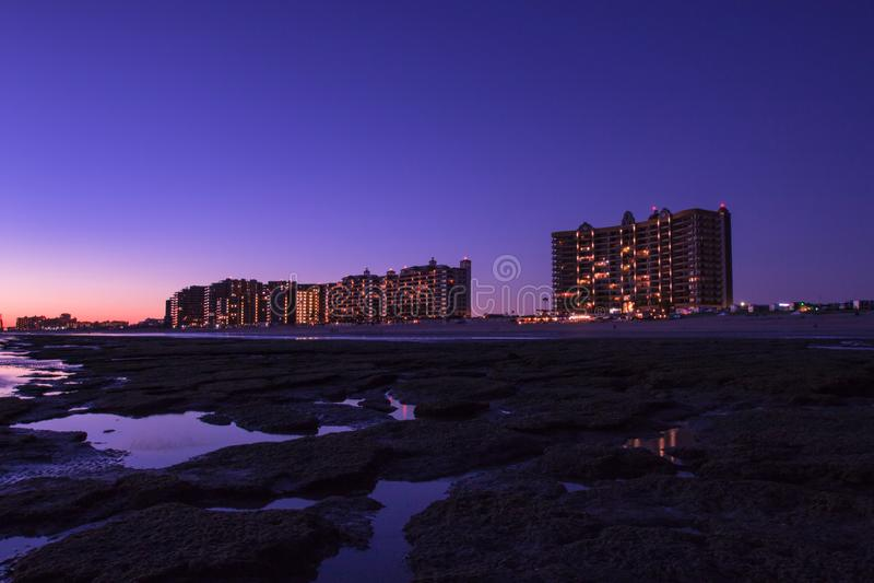 在一个多岩石的海滩的日落在前面旅馆 免版税库存照片