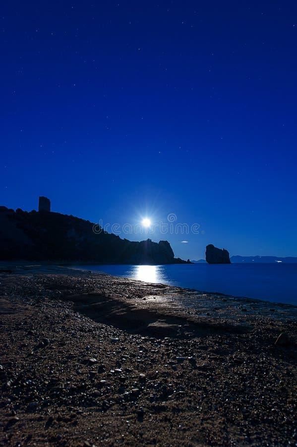 在一个多岩石的海滩的满月上升 库存图片