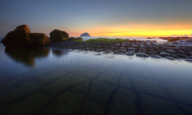 在一个多岩石的海滩的美好的日出风景与独特的象豆腐的岩层沿海 库存照片