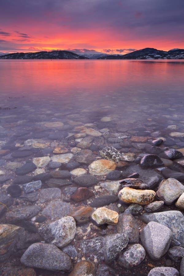 在一个多岩石的海滩的日落在北挪威 库存图片