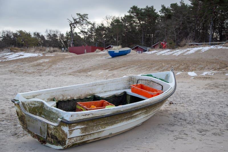 在一个多雪的海滩的一个渔船 免版税库存照片
