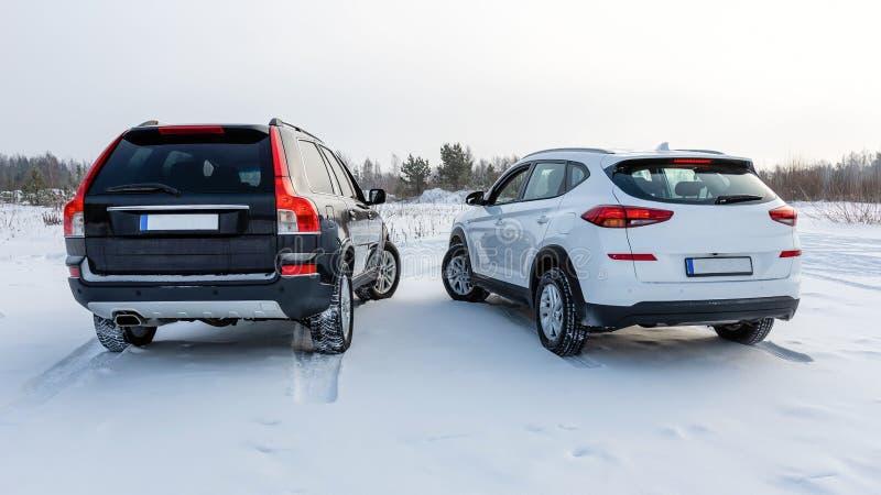 在一个多雪的领域停车场白色和黑suv 查出的背面图白色 免版税图库摄影