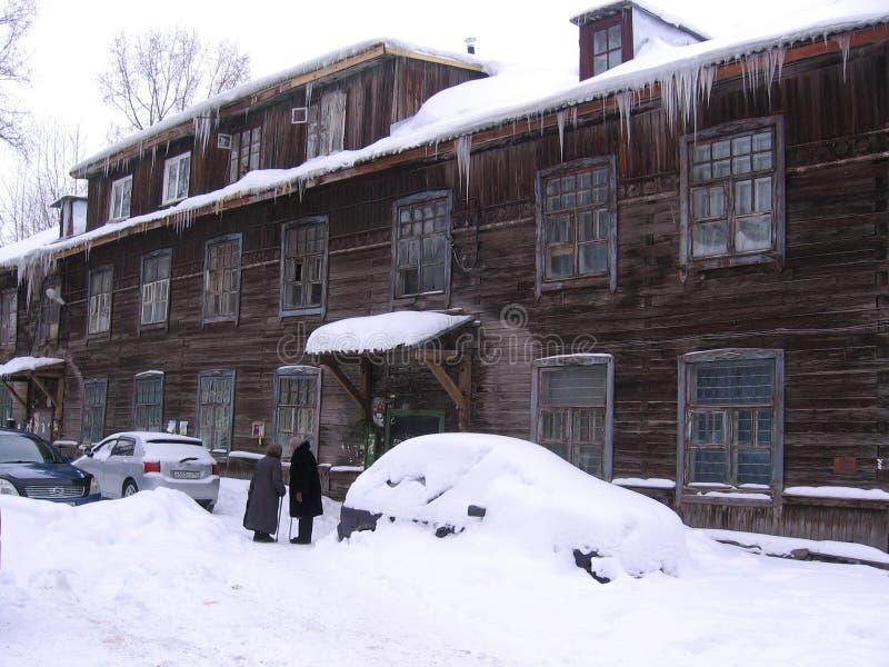 在一个大木房子附近的两个老妇人谈话在冬天 免版税库存照片