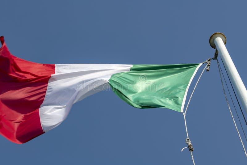 在一个大风天拍动的意大利旗子 免版税图库摄影