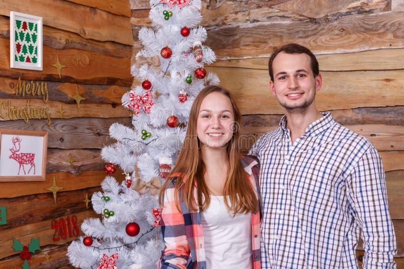 在一个女孩旁边的一个人在圣诞树特写镜头的背景中 库存照片