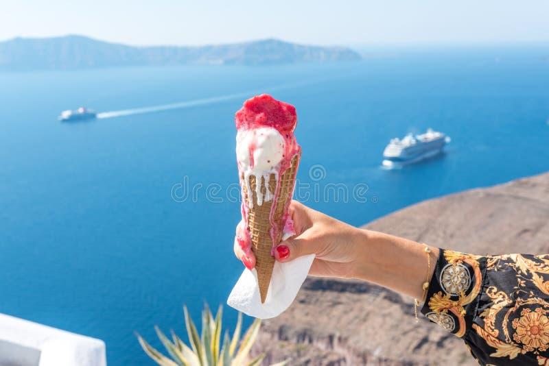在一个奶蛋烘饼锥体在妇女的手上在圣托里尼海岛背景和破火山口的冰淇淋在爱琴海 免版税库存照片