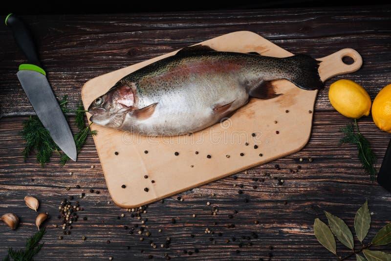 在一个委员会的未加工的鳟鱼在与成份的一张桌上烹调的 鱼新红色 库存照片