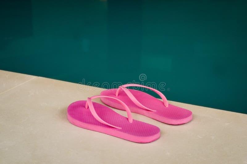 在一个室内游泳池的边缘的桃红色触发器 免版税库存照片