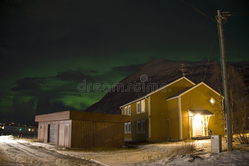 在一个家后被看见的北极光极光borealis在挪威的北部的一个小村庄 冬天中 库存照片
