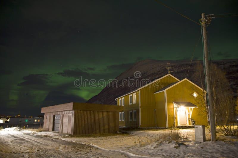 在一个家后被看见的北极光极光borealis在挪威的北部的一个小村庄 冬天中 免版税库存照片