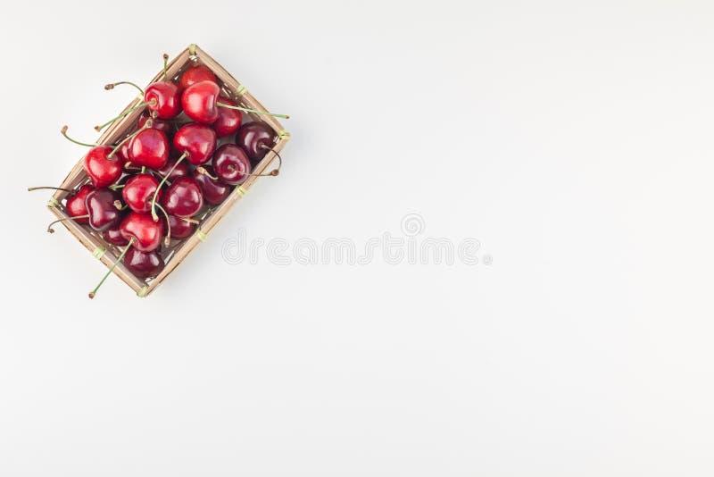 在一个小柳条筐的新鲜的成熟樱桃 免版税库存图片