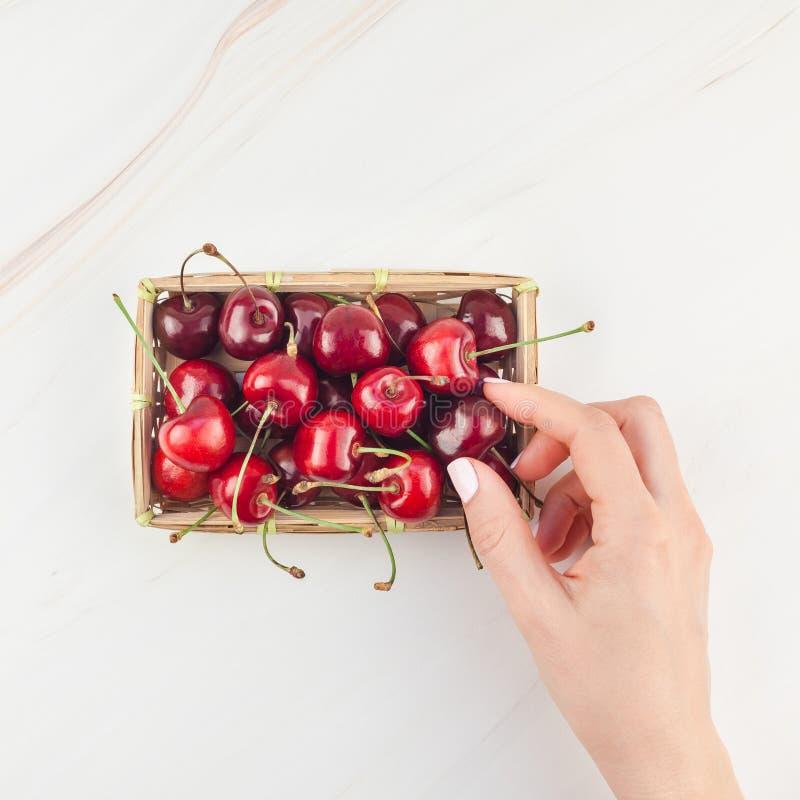 在一个小柳条筐的新鲜的成熟樱桃 图库摄影