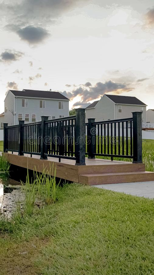 在一个小池塘的垂直的桥梁有树上小屋和coudy天空的看法在日落 库存图片