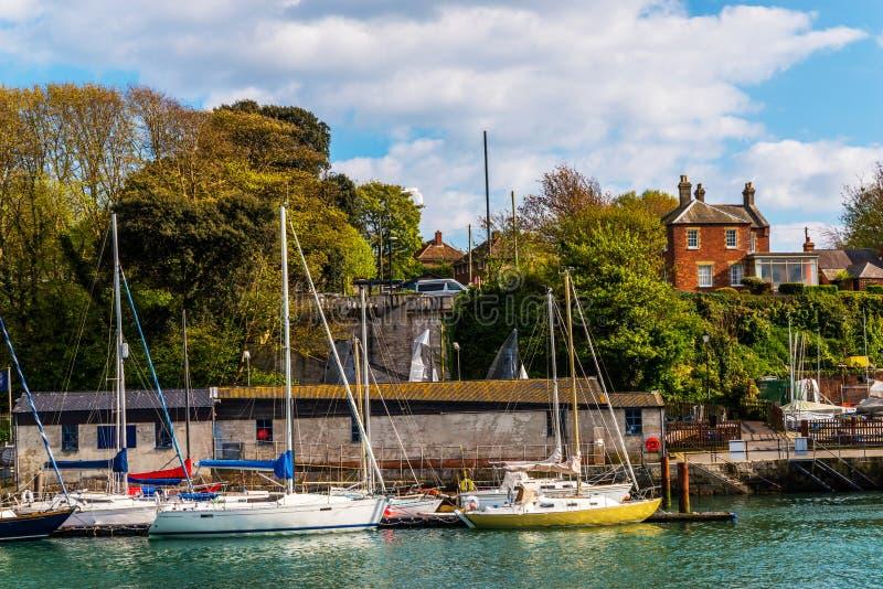在一个小港口停住的小船,背景石头buildi的 免版税图库摄影