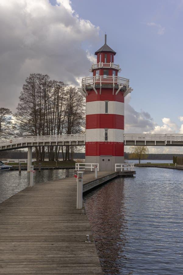 在一个小港口的一座红色和白色镶边灯塔有夏天村庄的在附近德国湖 库存图片