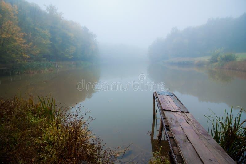 在一个小湖的有薄雾的秋天早晨,雾天气,在寂静的水表面,黄色树反射的木人行桥 库存图片