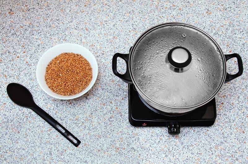 在一个小电火炉的平底深锅与一个被蒸的盒盖 在桌上有有碎荞麦片和匙子的一个碗 库存图片
