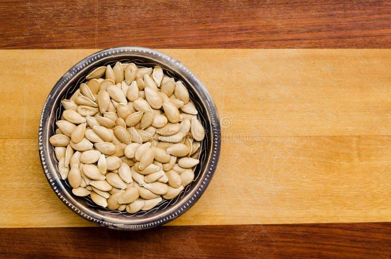 在一个小碗里面的南瓜籽两色木表面上 r 免版税库存图片