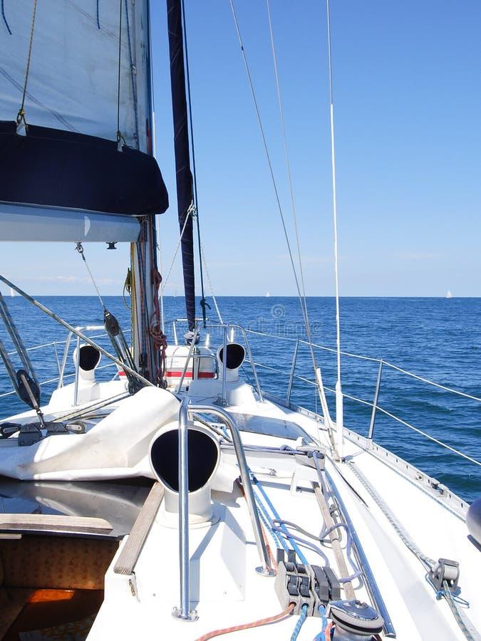 在一个小船航行的帆船设备在水在晴天 免版税库存图片