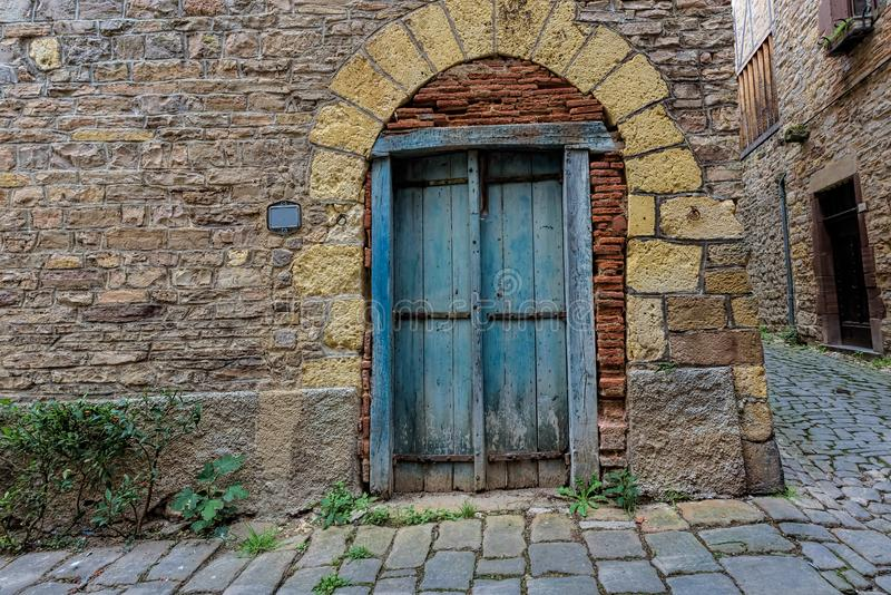 在一个小镇的石墙上的淡蓝和破旧的门在Fr 库存照片