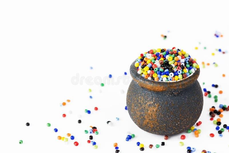 在一个小陶瓷罐的多彩多姿的小珠 库存图片